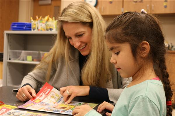 President and Chief Executive Officer Tiffany Kuehner helps Edison Elementary student select books.