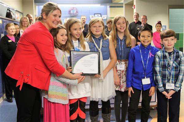 Lewis and Clark principal poses with students at the branch opening on Oct. 12.